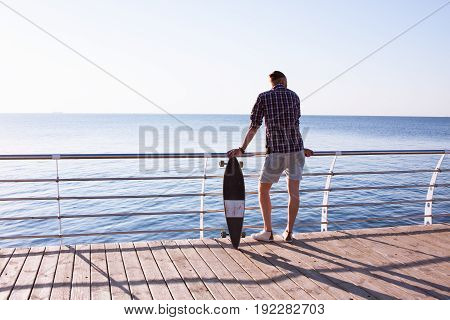 Young man stand alone with skateboard during sunrise, sea or ocean background