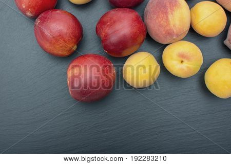 Ripe apricot and nectarine on black background of slate or stone.