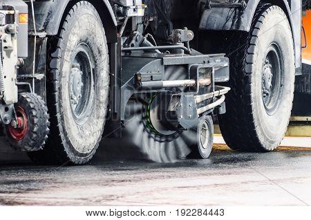 Brush cleaning roads wheels of the harvesting machine