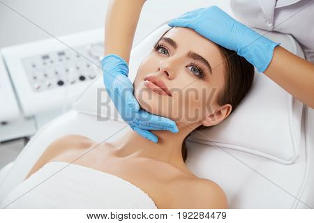 Doctor Massaging Face Of Young Woman