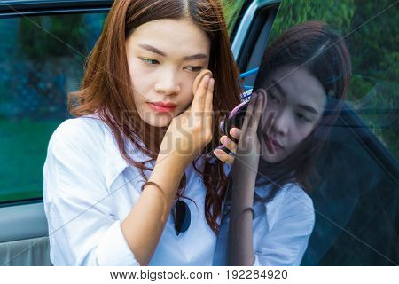 young attractive asian woman teen putting make up on her face outside of her car with her own reflection on the car window