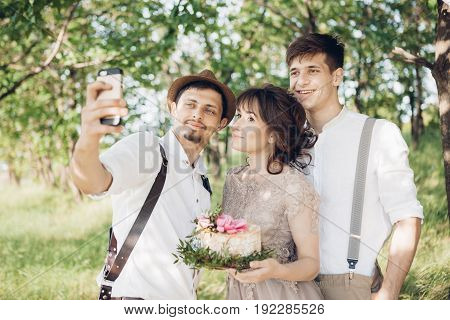 Wedding photographer, bride and groom make selfie in the nature