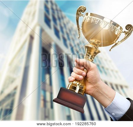 Holding golden trophy in hand sport competition