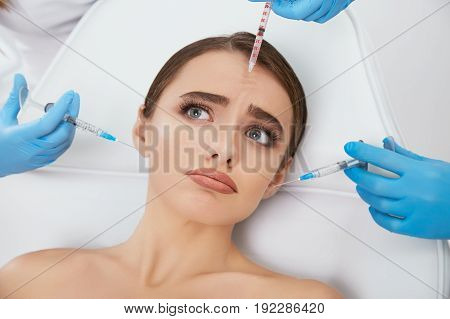 Doctor's Hands With Syringes Around Model