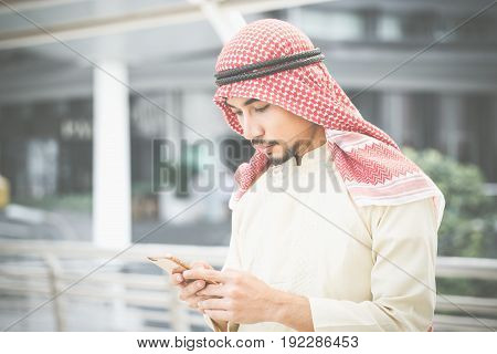 Arab businessman working with his phone behind the office building.