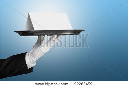Empty plate waiters hand holds on blue background