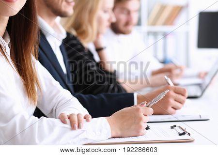 A group of people at the seminar listens attentively for good preparation and consolidation of knowledge received from the teacher make notes in notebooks and clipboards write the letter summary compiled correctly