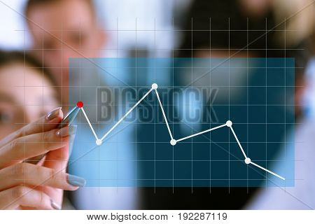 A Group Of People Examines The Financial Statistics Of An Enterprise Pointing With A Hand With A Pen