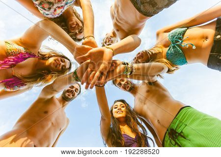 Group Of Friends With Hands On Stack At Seaside