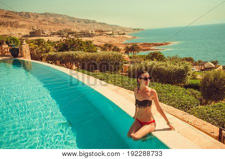 Caucasian sexy skinny model with thin waist relaxing in luxurious infinity pool. Young woman rest in spa resort. Summer luxury vacation. Tourism and travel concept. Enjoying suntan. Dead Sea, Jordan.