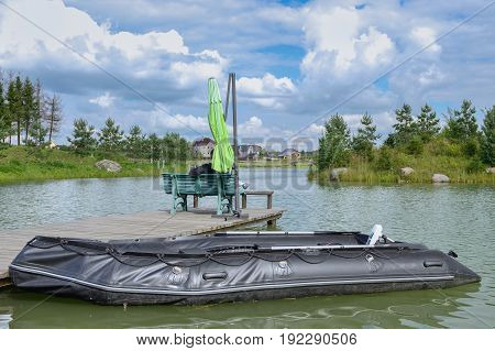 inflatable boat at the wooden pier on the lake