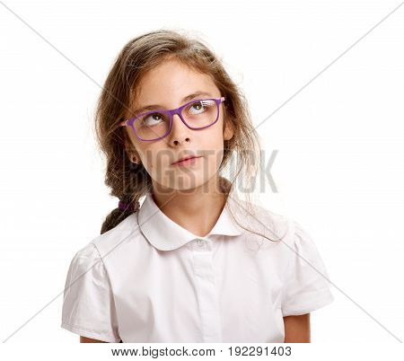 Portrait of young minded girl in glasses looking up