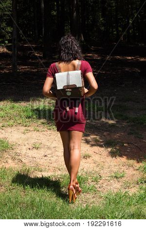 Woman in Red Dress and heels walking into the woods with her fashionable purse