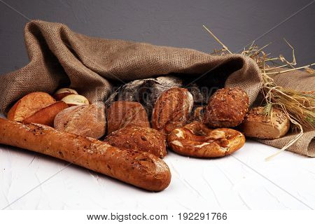Different Kinds Of Bread Rolls On White Board From Above. Kitchen Or Bakery Poster Design.