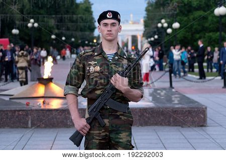 Yoshakr-Ola, Russia - June 21, 2017 Photo of the guard of honor with a Kalashnikov rifle in hand, near the memorial Eternal flame in the Central Park of Yoshkar-Ola, during the action Candle of Memory dedicated to the beginning of the Great Patriotic War