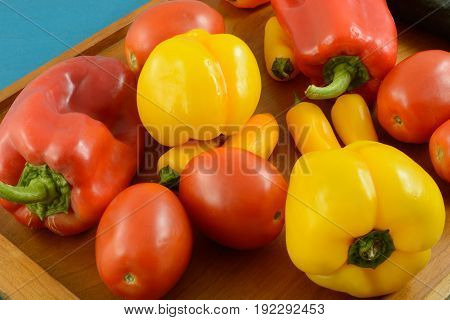 Tomatoes, bell peppers and sweet peppers on wooden tray