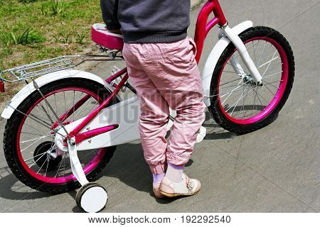 Sports kids outdoors. Girl stands near a pink child's Bicycle.