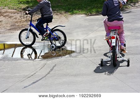 Sports kids outdoors. The girl and the boy ride through puddles on bikes.