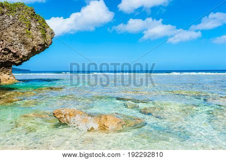 Sea water splashes around rock near beach on tropical patterns and intense colors of coral reef sea and sky