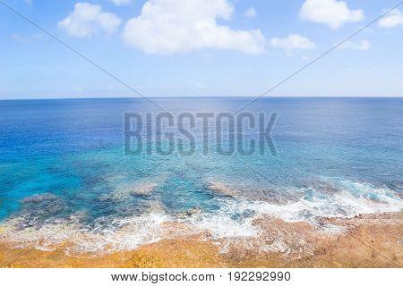 Pacific Ocean beyong coral shoreline and distant horizon and below sky.