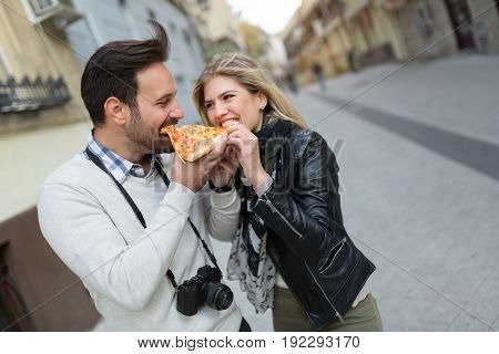Young attractive couple sharing pizza cut on street
