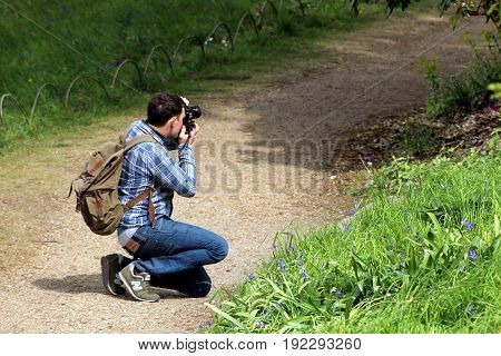 Wisley, Surrey, Uk - April 30 2017: Male Photographer In Checked Shirt, Kneeling On A Path To Take A