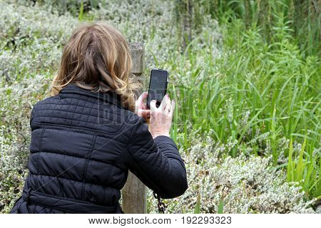 Wisley, Surrey, Uk - April 30 2017: Woman Taking A Photograph With A Mobile Phone