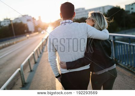 Happy young attractive couple spending time together on bridge