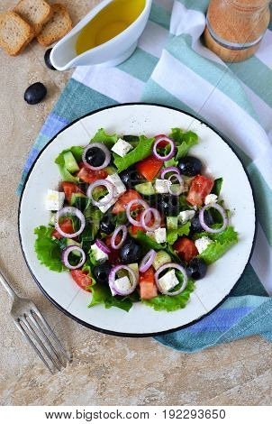 Classic Greek salad with sauce on a concrete background. Greek cuisine.