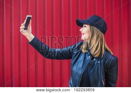 Attractive blond girl in leather black jacket and cap surfing the Internet on a mobile phone on a building background.