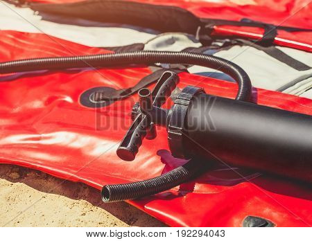 The plastic pump lies on a blown boat for kayaking on the beach. Water sports and equipment.