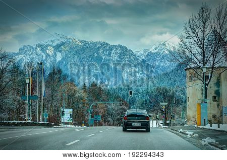 GERMANY, JAN, 12, 2013: View on a car on winter German road trees and Alpine mountains. Dramatic sky atmosphere aura. German autobahn. Car travel trip journey. Road way background. Dramatic colors