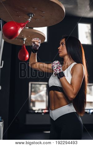 Sexy fighter girl punching actively. Strong athletic woman with boxing pear.
