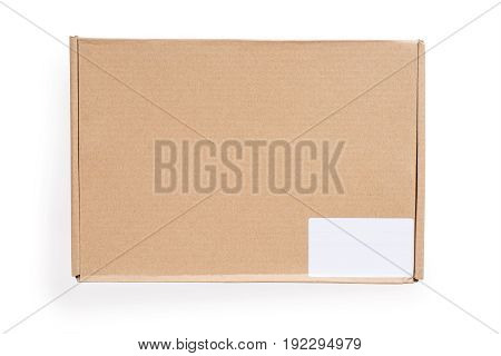 Closed cardboard box with blank white label. Isolated on white clipping path included. Top view