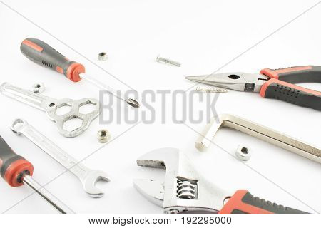 Screwdrivers wrenches tweezers with nuts and bolts.