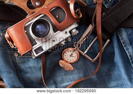 Old retro camera and pocket watch lies on a jeans