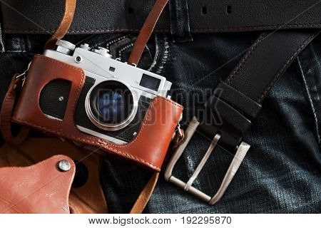 Old retro camera lies on a jeans
