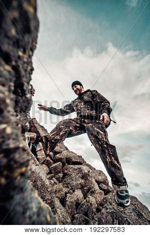 Man With A Backpack In Camouflage Rises To The Top Of The Mountain