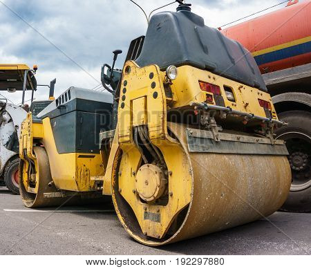 Yellow construction tractor road roller on the background of the technique for laying asphalt