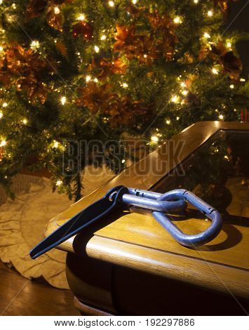 Piton and carabiners on a table with a Christmas tree behind