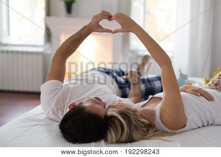 Young happy couple having romantic times on bed