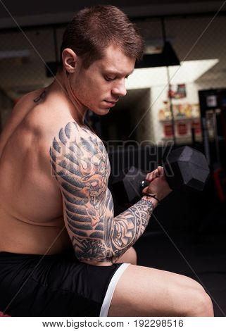 Bodybuilder man with naked torso and tattoos performing biceps training at the gym
