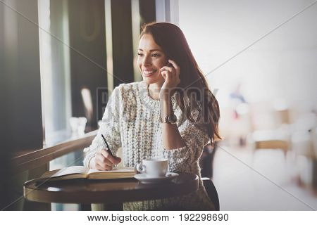 Attractive and beautiful woman talking on phone in restaurant