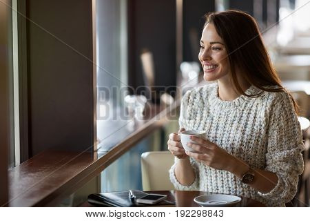 Attractive and beautiful woman drinking coffee in restaurant alone