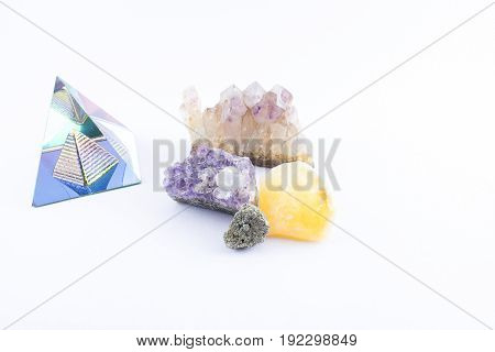 Pyramid and different types of precious stones on a white background.