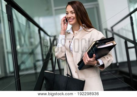 Attractive and beautiful woman in business talking on cellphone at office