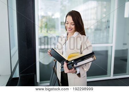 Attractive and beautiful businesswoman smiling and standing in office