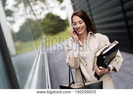 Attractive and beautiful businesswoman walking and talking on cellphone