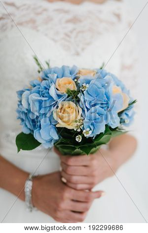 beautiful blue and yellow fresh flowers wedding bouquet. Bride with wedding bouquet, closeup.