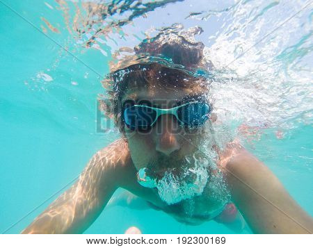 Underwater View Of A Man Swimming In The Sea